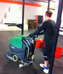person disinfecting and cleaning a rubber gym mat with the a Bulldog floor scrubber