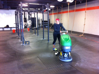 person cleaning and disinfecting gym mats with an industrial floor scrubber